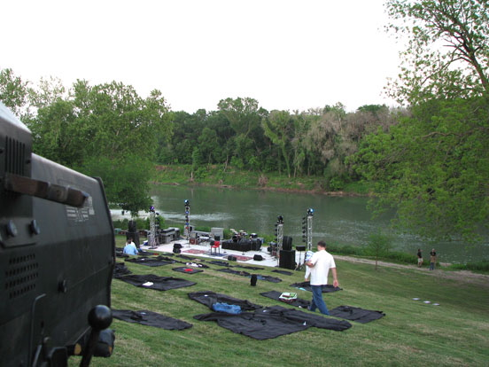 Stage being set up and blankets laid out on the grass for the DPM Lee Ann Womack concert at the Hyatt Lost Pines