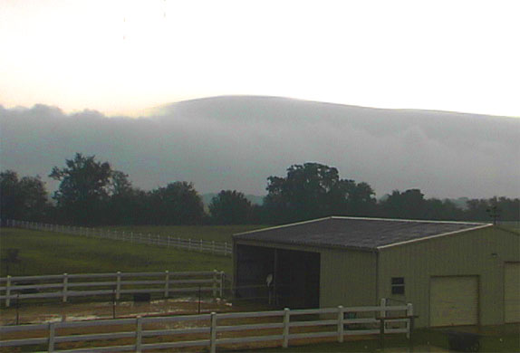 picture of clouds behind stable